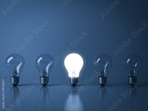 creative lighting concepts commercial lighting one glowing light bulb standing out from the crowd unlit incandescent bulbs on dark blue background