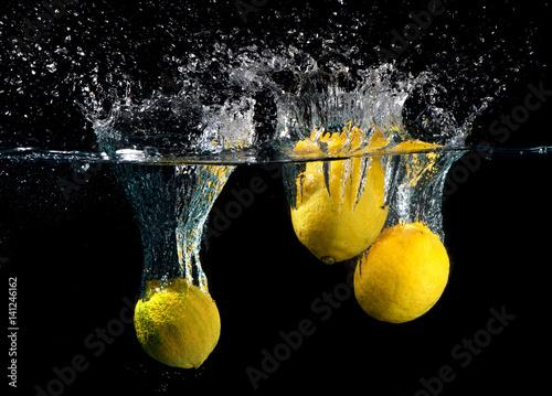 trzy-cytryny-pod-woda-i-rozbryzgujaca-woda-na-czarnym-tle