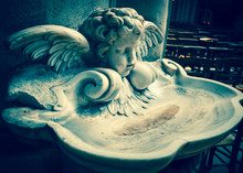 Baby Angel Over Holy Water Stoup In Church. Toned Photo.