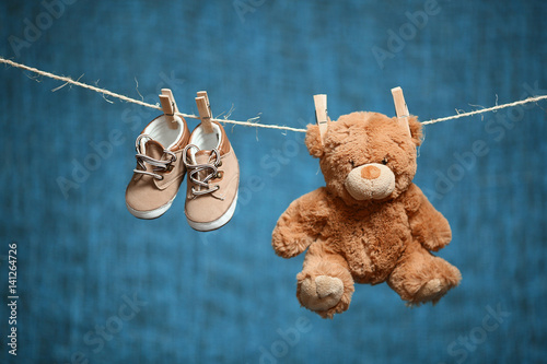 brown toy bear and baby shoes hanging on a rope on a blue background #141264726
