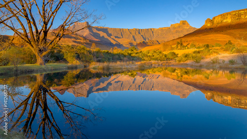 Photo Drakensberg mountains of the amphitheatre reflected in a lake early on a mid-win