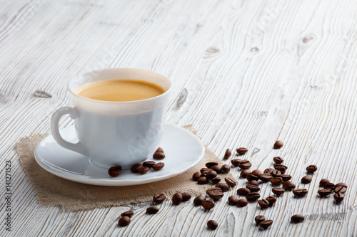 Photo sur Toile Salle de cafe Coffee cup and beans on a white wood background.