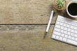 Top view of Office desk wood table with keyboard,green flower ,smart phone,watch,blank notebook and eyeglasses