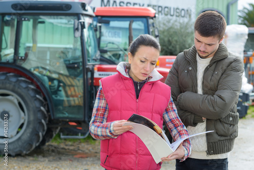 Fotografiet  saleswoman convincing young famrer to buy new agricultural machinery