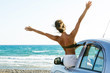 Happy woman and car on the beach
