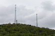 Telecommunication tower atop a mountain full of lush green trees.