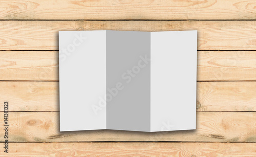 blank trifold white template paper on wood background with soft