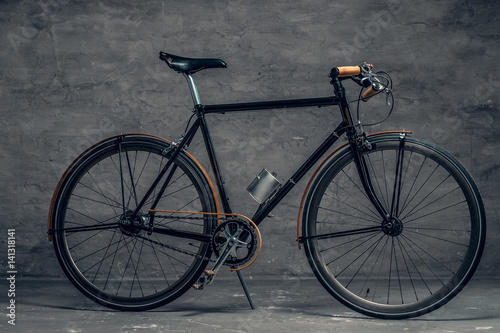 An authentic vintage single speed bicycle over grey background.