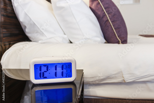 Photo  Alarm clock electronic stands on a bedside table near the bed