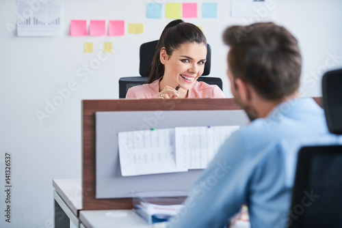 Office flirt - attractive woman flirting over desk with her coworker Tablou Canvas
