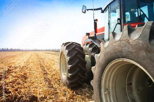 Modern red tractor in the field close-up.