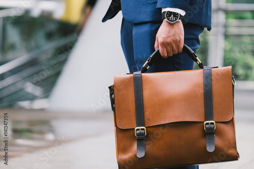Photo Closeup Of A Businessman wear the watch and Holding leather Briefcase Going To W