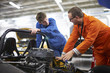 College mechanic students discussing racing car engine in repair garage