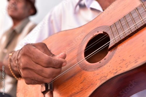 Street musician playing traditional cuban music on an acoustic guitar for the en Fototapeta