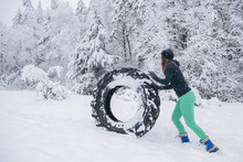 Woman Rolling Tire Through Snow