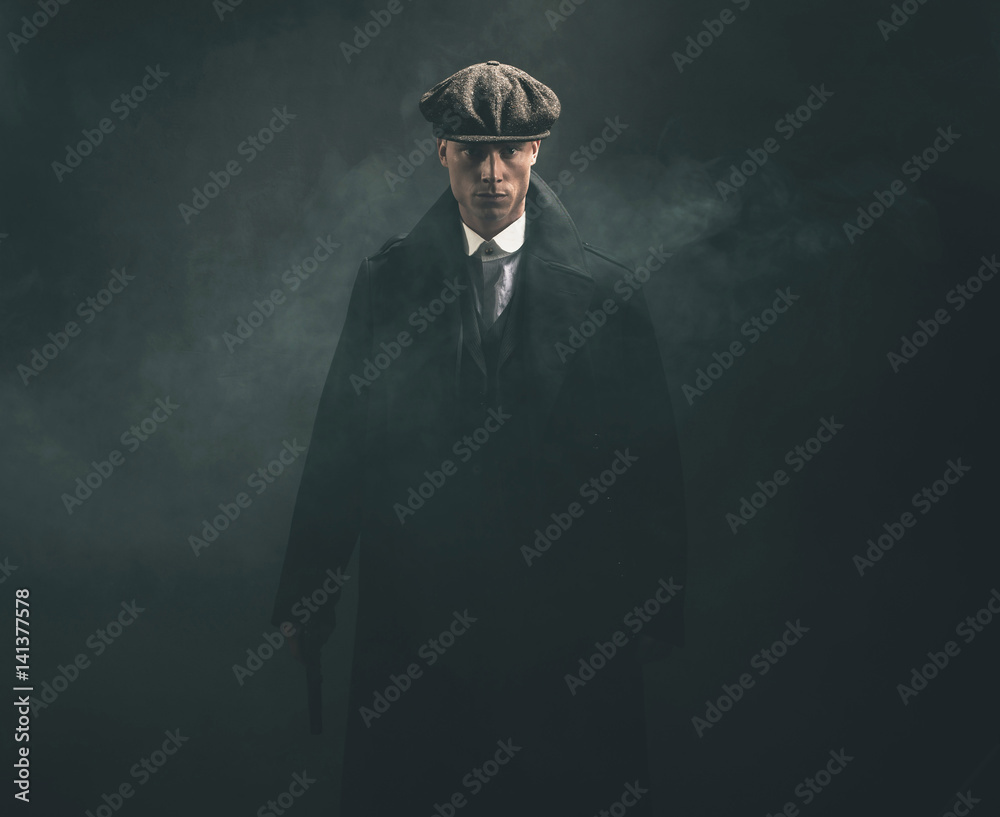 Fototapeta Threatening retro 1920s english gangster holding gun in smoky room.
