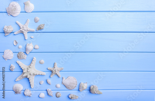 Shells and starfish on blue boards.
