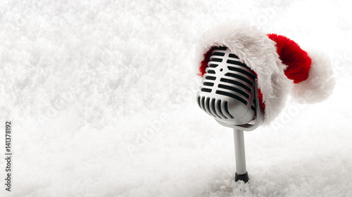 Fotografía  Carols and Christmas music concept with a microphone wearing a santa hat isolate