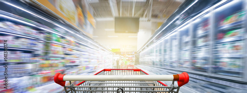 Fotografía Supermarket aisle with empty red shopping cart