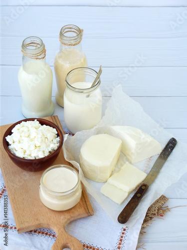 Staande foto Zuivelproducten Set of fresh dairy products on wooden background: milk, cheese, cottage, yogurt, egg, mozzarella, ryazhenka, feta.