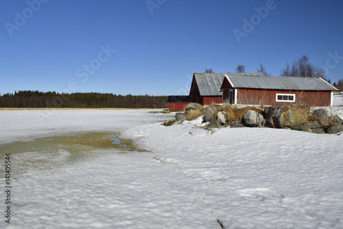 Fotografie, Obraz  Melting sea ice in spring sun and rocks and three red boathouse