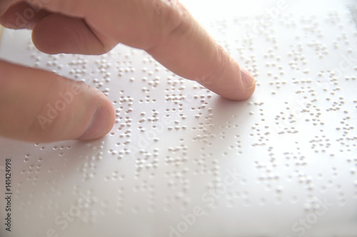 Fotografija  Hand of a blind person reading some braille text touching the relief