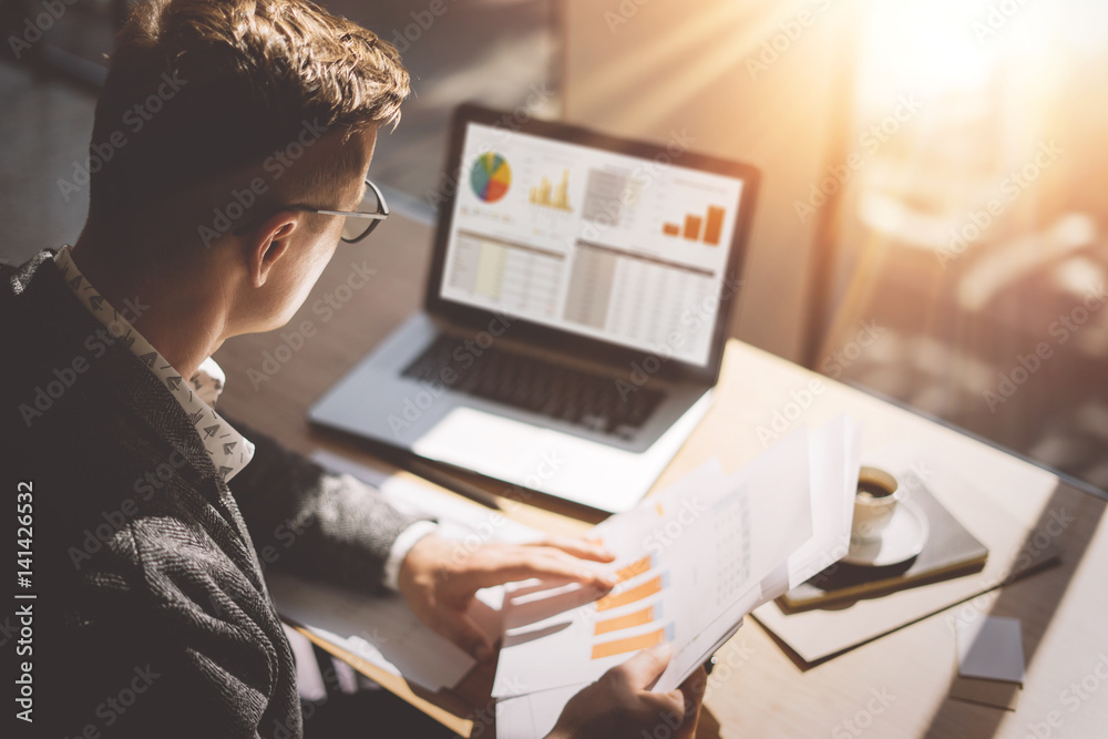 Fototapeta Young finance market analyst in eyeglasses working at sunny office on laptop while sitting at wooden table.Businessman analyze document in his hands.Graphs and diagramm on notebook screen.Blurred.
