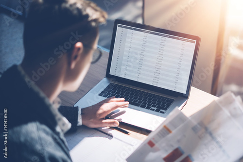Closeup view of banking finance analyst in eyeglasses working at sunny office on laptop while sitting at wooden table Wallpaper Mural