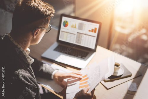 Young finance market analyst in eyeglasses working at sunny office on laptop while sitting at wooden table Wallpaper Mural