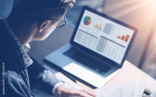Fotografía  Closeup view of finance market analyst in eyeglasses working at sunny office on laptop while sitting at wooden table