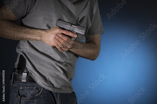 Fotografía  Man drawing a concealed carry pistol from a holster