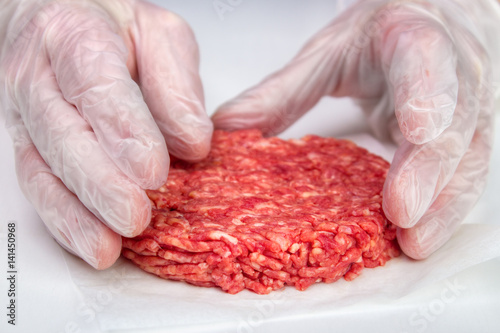 Fotografie, Obraz  Hand shaping burger patty with vinyl gloves for hygiene