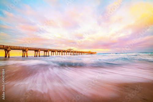 Pier lit by the rays of the sun at sunset, dawn on the ocean shore. A wave striking the shore shot at a long exposure. A beautiful sky with orange clouds. USA. Florida.