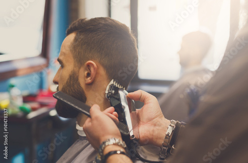 Fotografia Man getting haircut by hairstylist at barbershop