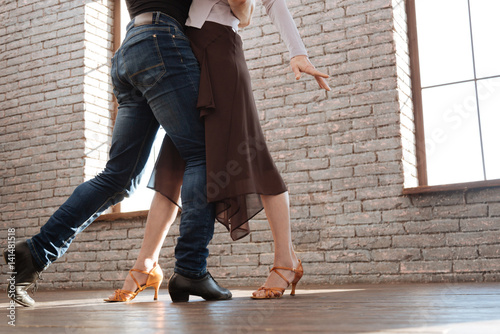 Graceful dance couple tangoing at the ballroom