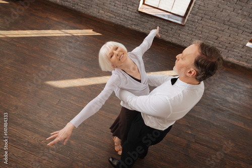 Optimistic retired dance couple enjoying waltz in the dance studio Fototapete