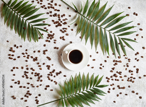 Cup of black espresso on a white creative concrete background with coffee beans and palm branches. Rest in warm tropical countries concept. Flat lay drink composition.