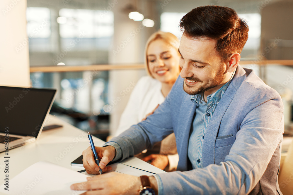 Fototapeta Young business couple signing a contract