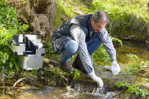 Fotografía  View of a Biologist take a sample in a river.