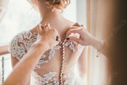 Valokuva  Bridesmaid preparing bride for the wedding day