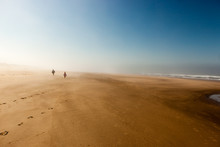 Figures In The Mist At On A Sandy Misty Beach