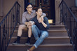 Homosexual couple relaxing on steps,