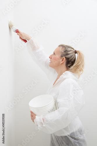 Fotografie, Obraz  bella ragazza dipinge una parete di bianco