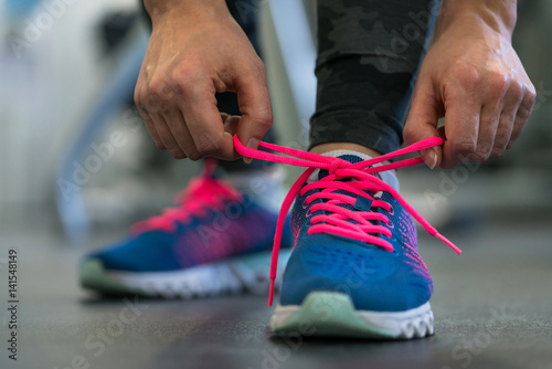 Fotomural  Running shoes - woman tying shoe laces