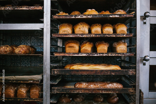 In de dag Bakkerij A lot of ready-made fresh bread in a bakery oven in a bakery. Bread making business. Fresh bread from cereals with seeds from a bakery. Healthy and nutritious food. The product contains carbohydrates.