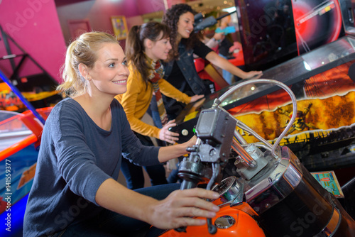 Fotografiet Woman on arcade motorcycle