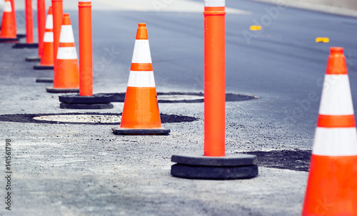 Fotografie, Obraz  Orange Cones in a Row by the Side of a Street
