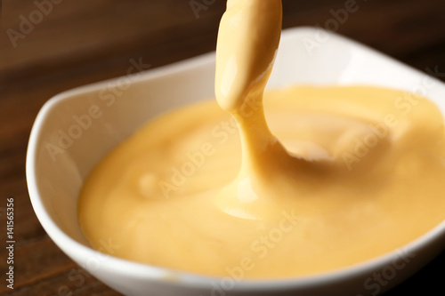 Crunchy fries with tasty cheese sauce, closeup