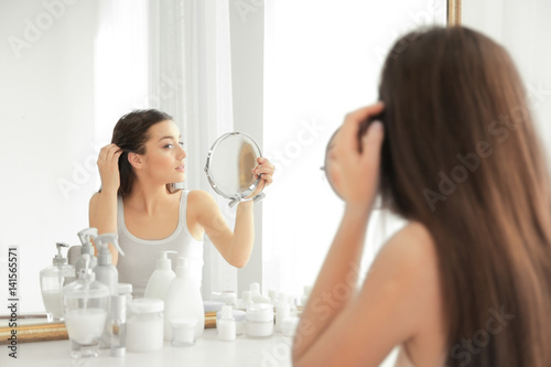 Valokuva  Young woman with hair loss problem in front of mirror at home