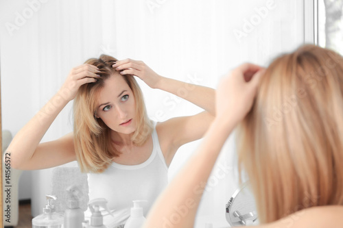 Young woman with hair loss problem looking in mirror at home Canvas Print